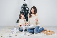 Мать и маленькая дочь пакуют подарки стоковые изображения