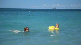 Мать и маленький сын наслаждаясь играть в море Мальчик женщины закручивая excited в резиновом кольце Потеха семьи во время лета акции видеоматериалы