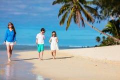 Мать и малыши на тропическом пляже Стоковые Изображения