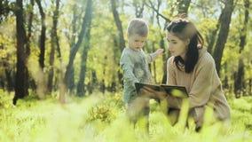 Мать и мальчик сидят в лужайке осени и читают книгу видеоматериал