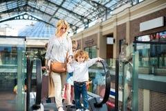 Мать и мать детей при дети поднимая на эскалатор с хозяйственными сумками Стоковое Изображение