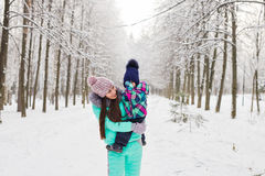 Мать и маленькая девушка малыша идя в лес зимы и имея потеху с снегом наслаждаться зимой семьи Рождество Стоковое фото RF