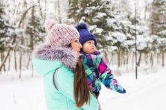 Мать и маленькая девушка малыша идя в лес зимы и имея потеху с снегом наслаждаться зимой семьи Рождество Стоковые Фото