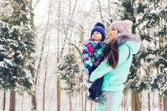 Мать и маленькая девушка малыша идя в лес зимы и имея потеху с снегом наслаждаться зимой семьи Рождество Стоковое Фото