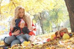 Мать и маленький ребёнок играя в осени паркуют стоковое изображение rf