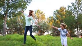 Мать и маленький сын бежать через зеленый парк видеоматериал
