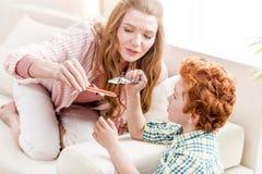 Мать и маленький сын играя с игрушками дома, потеха семьи стоковое фото