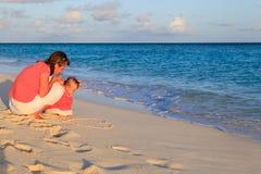 Мать и маленькое сердце чертежа дочери на пляже Стоковое Изображение