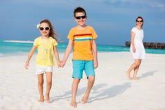 Мать и малыши на тропическом пляже Стоковое Изображение