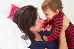 Мать и малыш лежа в кровати совместно стоковое изображение rf