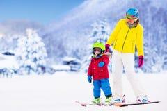 Мать и мальчик уча кататься на лыжах Стоковое фото RF