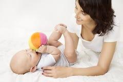 Мать и младенец играя шарик игрушки, игру ребенк новорожденного с мамой Стоковые Изображения