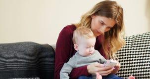 Мать и младенец используя мобильный телефон на софе 4k сток-видео