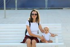 Мать и младенец сидя на стенде стоковое фото