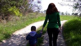 Мать и молодой сын идут на дорогу в лесе видеоматериал