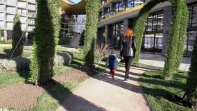 Мать и молодой сын идут через парк на улице акции видеоматериалы