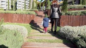 Мать и молодой сын идут через парк на улице сток-видео