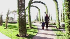 Мать и молодой сын идут через парк видеоматериал
