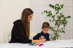 Мать и молодой сын рисуют изображение на таблице стоковые изображения rf