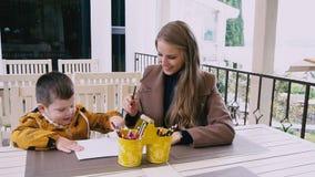 Мать и молодой сын рисуют на таблице сток-видео