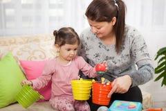 Мать и молодая дочь играя с игрушками в живущей комнате Стоковые Изображения RF