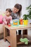 Мать и молодая дочь играя с игрушками в живущей комнате Стоковое Фото