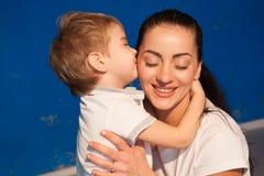 Мать и молодой поцелуй объятия сына стоковые изображения rf