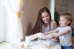Мать и молодой сын подготавливают пирог в кухне стоковые фото