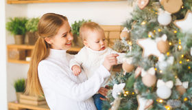 Мать и младенец семьи украшают рождественскую елку Стоковая Фотография