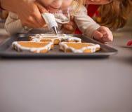 Мать и младенец украшая печенья рождества с поливой Стоковое Изображение RF