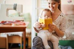 Мать и младенец читая книгу совместно дома Стоковые Изображения RF