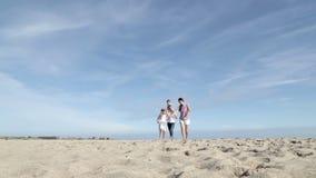 Мать и отец закручивая их сына и дочери на пляже видеоматериал