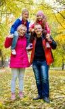 Мать и отец нося 2 милых детей на плечах Стоковые Изображения RF