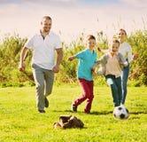 Мать и отец при 2 дет бежать после шарика Стоковая Фотография