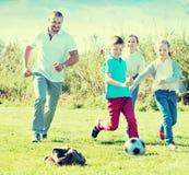 Мать и отец при 2 дет бежать после шарика Стоковые Изображения