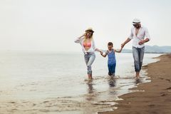 Мать и отец с их сыном идя совместно на пляж стоковое фото rf
