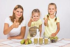 Мать и 2 дочери показывают большие пальцы руки вверх путем подготавливать свеже сжиманный сок Стоковые Фото