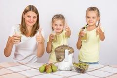 Мать и 2 дочери показывают сок больших пальцев руки вверх свеже подготовленный Стоковые Изображения