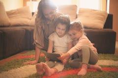 Мать и дочери читая на таблетке Стоковые Фото