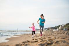 Мать и дочь бежать на пляже на заходе солнца Стоковые Изображения RF