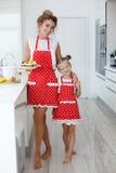 Мать и дочь варя пирожные на праздничной таблице Стоковое Изображение