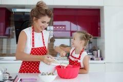 Мать и дочь варя пирожные на праздничной таблице Стоковое фото RF