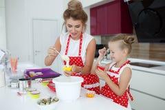 Мать и дочь варя пирожные на праздничной таблице Стоковое Изображение RF