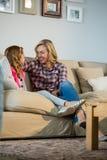 Мать и дочь взаимодействуя друг с другом в живущей комнате стоковая фотография