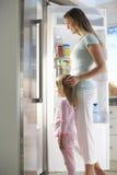 Мать и дочь выбирая закуску от холодильника Стоковые Изображения