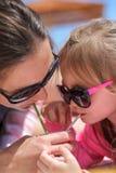 Мать и дочь выпивая коктеиль от одного thro стеклянной лампы Стоковые Фото