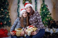 Мать и дочь в крышках с серией подарков стоковые фото