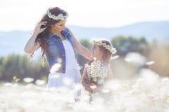 Мать и дочь в поле лета зацветая маргариток Стоковая Фотография