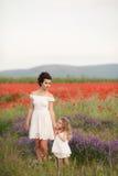 Мать и дочь в поле зацветая маков Стоковые Фотографии RF