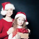 Мать и дочь в шляпе Санты держа подарок рождества Стоковые Фото